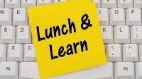 Lunch and Learn Computer Keyboard with a yellow blank sticky note with text Lunch and Learn